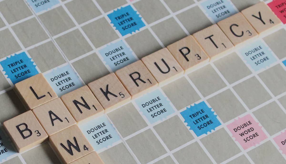 """Bankruptcy"" and ""Law"" words placed on a Scrabble game board."