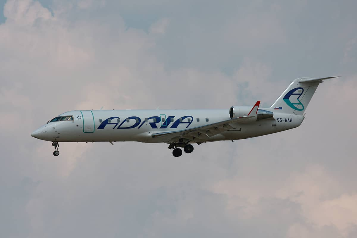 "A flying white ""Bombardier"" aircraft with Adria Airways logo."