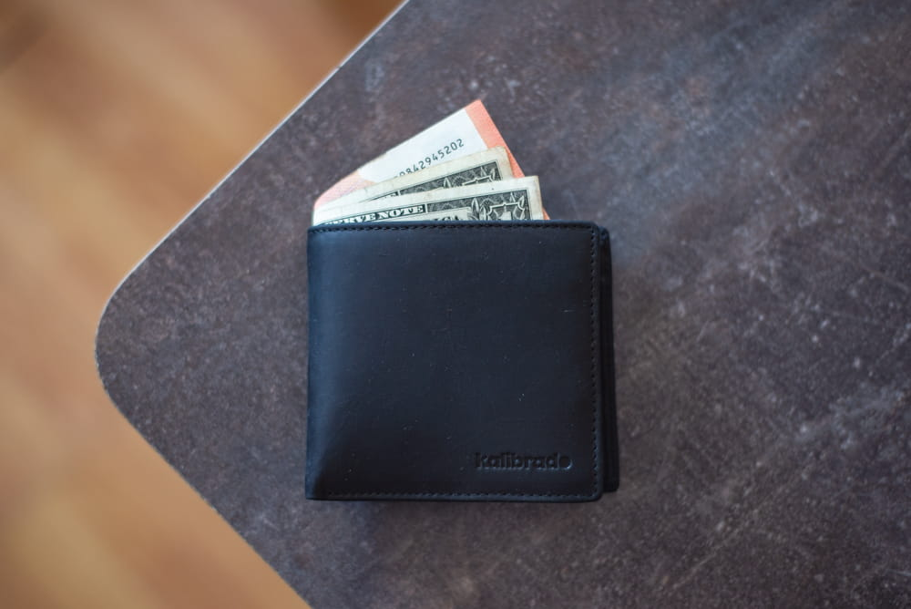 A black leather wallet on a table with money sticking out.