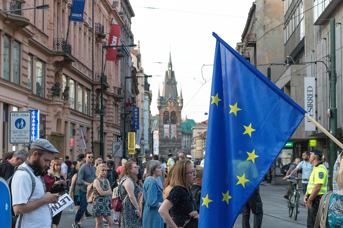 People walking on a square waiving the EU flag