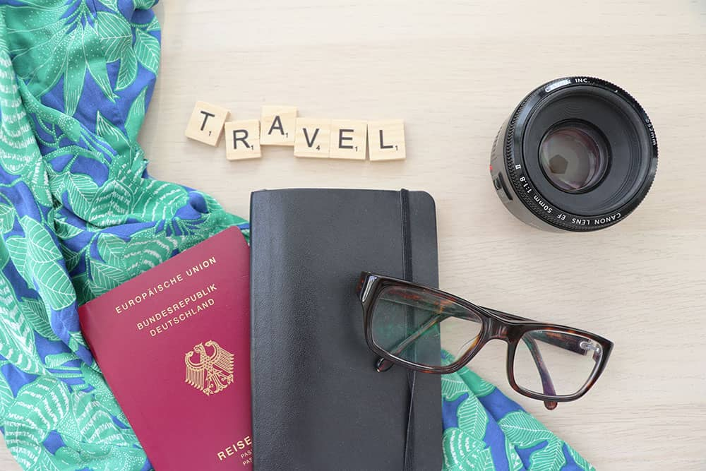 A collection of travel items: passport, glasses, camera and a notebook.
