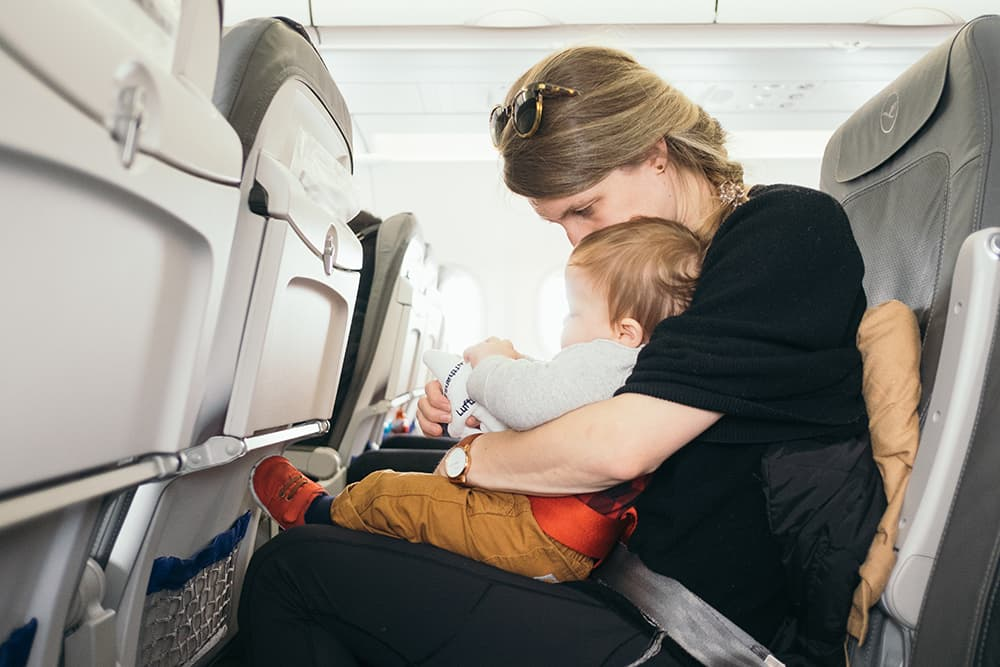 A mother holding her baby on-board a plane.