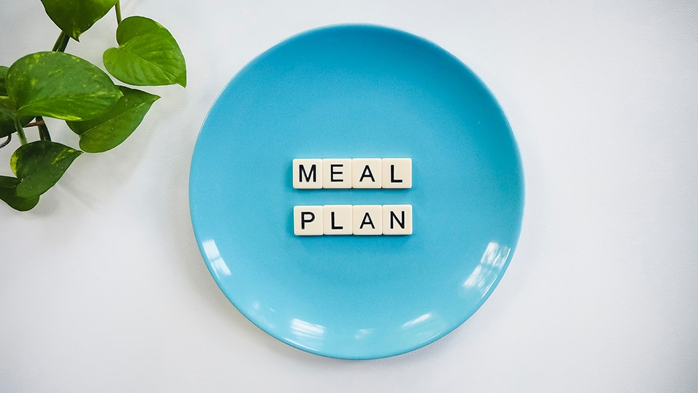 "A blue bowl with scrabble letters inside saying ""plan meal""."