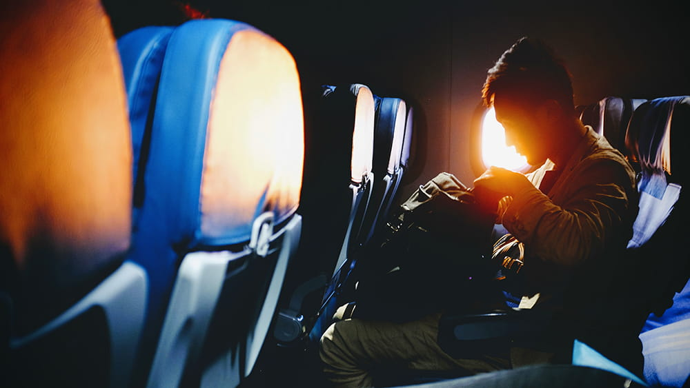 A man on a plane looking inside his bag.