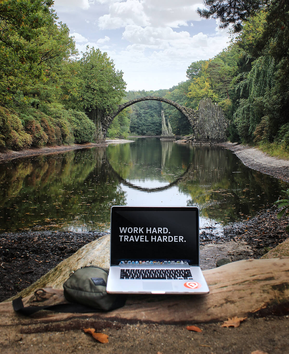 "An open laptop with a motivational quote on screen saying ""Work hard, travel harder"" on a river background."