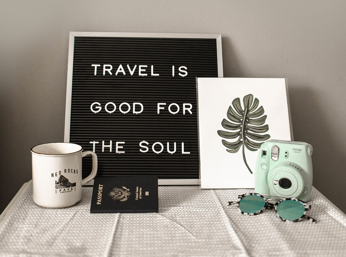 "A passport, cup, camera and a painting saying ""Travel is good for the soul""."
