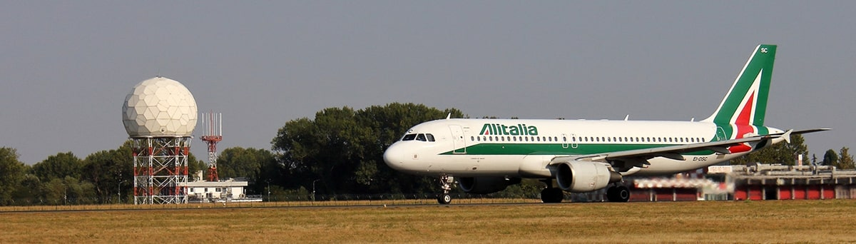 A white and green Alitalia aircraft taxiing on the runway.