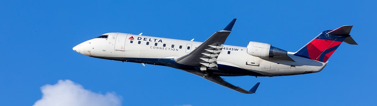 A flying Delta airplane on blue sky background.