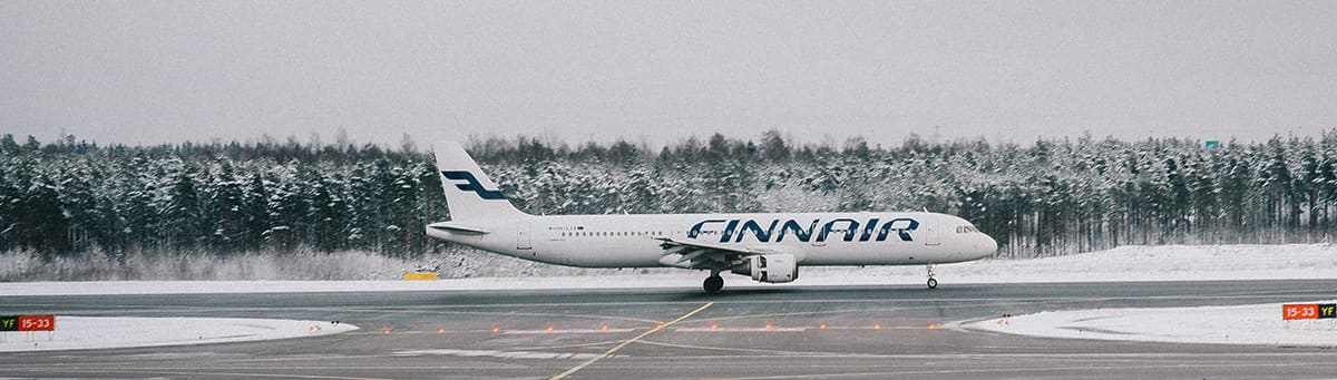 A white Finnair aircraft taxiing on a runway cover with snow.