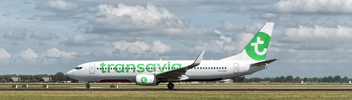 A white and green Transavia aircraft taxiing on the runway.