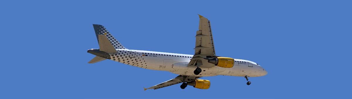 A white Vueling aircraft in-flight on a blue sky background..